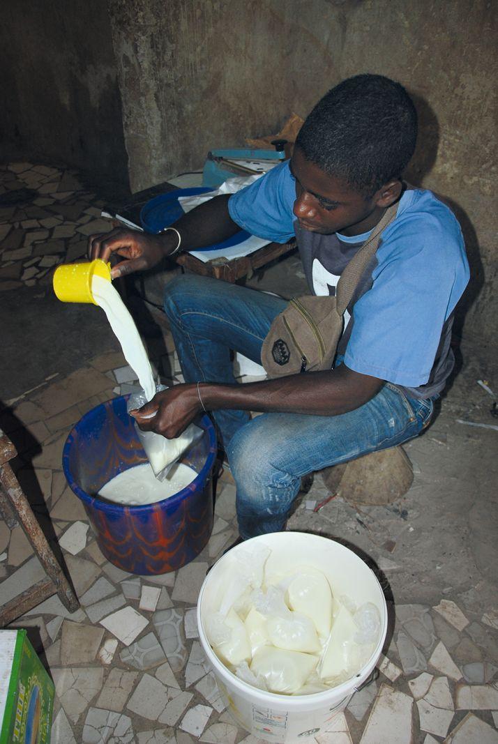Thierno remplit les sachets de lait chez Saïdou.